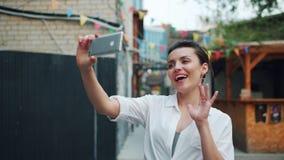 采取selfie的俏丽的夫人的慢动作外面使用智能手机挥动的手 股票视频