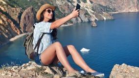 采取selfie的可爱的年轻旅行妇女使用摆在海景背景的智能手机 股票录像