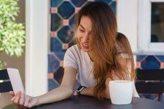 采取selfie的可爱的美丽的愉快的年轻亚裔妇女使用一个巧妙的电话在咖啡馆 免版税库存图片