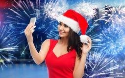 采取selfie的圣诞老人帽子的妇女由智能手机 免版税库存图片
