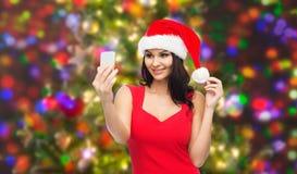 采取selfie的圣诞老人帽子的妇女由智能手机 库存照片