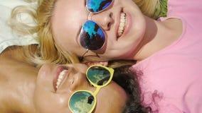 采取selfie的太阳镜的微笑的女孩一起说谎在草,友谊 影视素材