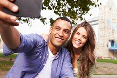 采取Selfie的夫妇由塔桥梁在伦敦 免版税库存图片