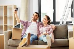 采取selfie的夫妇由智能手机在新的家 库存照片