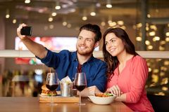 采取selfie的夫妇由智能手机在餐馆 库存图片