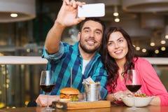采取selfie的夫妇由智能手机在餐馆 库存照片