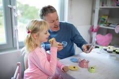 采取selfie的女孩和父亲,当使用与玩具厨房集合时 免版税库存照片