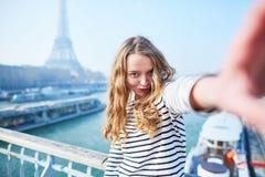 采取selfie的女孩在埃佛尔铁塔附近 库存照片