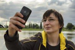 采取selfie的妇女使用巧妙的电话 库存图片