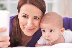 采取selfie的妇女和她的婴孩 库存照片