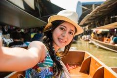 采取selfie的妇女浮动市场假日 库存照片