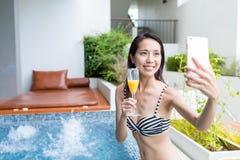 采取selfie的妇女由在极可意浴缸温泉的手机 库存照片