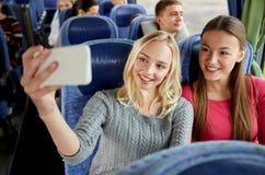 采取selfie的妇女由智能手机在旅行公共汽车上 免版税库存图片