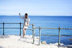 采取selfie的妇女由海 免版税图库摄影