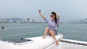 采取selfie的妇女,当享受在游艇时的巡航 股票录像