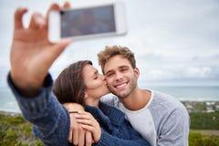 采取selfie的妇女,当亲吻她的他的面颊的时男朋友 免版税图库摄影