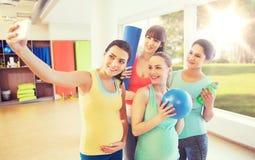 采取selfie的孕妇由在健身房的智能手机 库存图片
