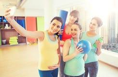 采取selfie的孕妇由在健身房的智能手机 库存照片