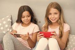 采取selfie的孩子 智能手机应用概念 少女休闲睡衣派对 女孩智能手机小博客作者 库存照片