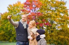 采取selfie的家庭由智能手机在秋天公园 图库摄影