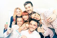 采取selfie的小组愉快的商人在办公室 库存图片