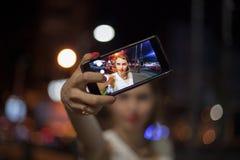 采取selfie的少妇在城市 免版税库存图片