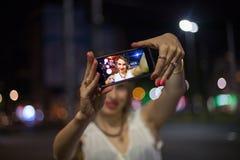 采取selfie的少妇在城市 库存图片