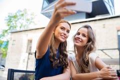 采取selfie的少妇由智能手机在咖啡馆 库存照片
