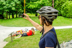 采取Selfie的少妇骑自行车者在公园 免版税库存图片