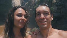 采取selfie的年轻家庭游人在美丽的瀑布附近在密林在巴厘岛 夫妇亲吻并且拍照片 股票视频
