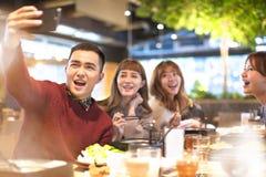 采取selfie的年轻小组在餐馆 库存照片