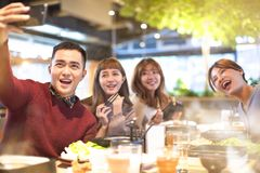 采取selfie的年轻小组在餐馆 免版税库存照片