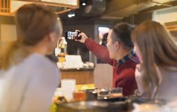 采取selfie的年轻小组在餐馆 免版税库存图片