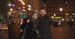 采取selfie的年轻美好的夫妇在城市在晚上 股票录像