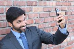 采取selfie的微笑的商人 免版税库存照片