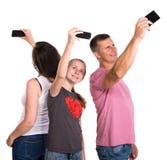 采取selfie的微笑的父亲、母亲和女儿由智能手机 库存图片
