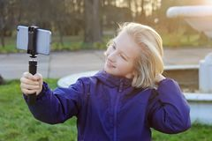 采取selfie的微笑的美丽的青春期前的女孩户外 采取与手机的孩子一张自画象 库存照片