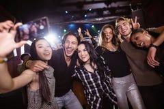 采取selfie的快乐的朋友,当享用在夜总会时 库存图片