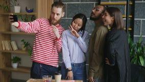 采取selfie的愉快的不同种族的队在现代顶楼办公室 举行智能手机与他的行家人作为自画象 影视素材