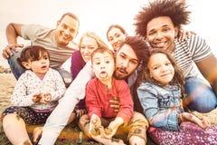 采取selfie的愉快的多种族家庭在做滑稽的面孔的海滩 免版税库存照片