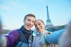 采取selfie的愉快的夫妇在埃佛尔铁塔附近 免版税库存图片