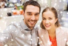 采取selfie的愉快的夫妇在购物中心或办公室 库存图片