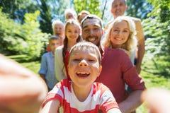 采取selfie的愉快的家庭在夏天庭院里 库存图片