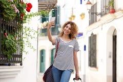 采取selfie的愉快的年轻人旅行妇女外面 库存照片