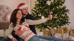 采取selfie的愉快的年轻夫妇装饰为圣诞节室 概念新年好 可爱的系列 股票视频