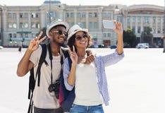 采取selfie的愉快的非裔美国人的游人在新的城市 库存图片
