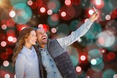 采取selfie的愉快的年轻夫妇的综合图象 库存图片