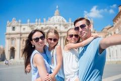 采取selfie的愉快的年轻家庭在圣皮特圣徒・彼得的大教堂教会在梵蒂冈,罗马 愉快的旅行父母和孩子 库存图片