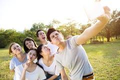 采取selfie的愉快的年轻小组在公园 图库摄影