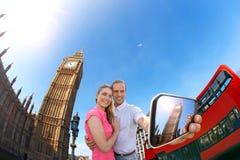 采取selfie的旅游夫妇反对大本钟在伦敦,英国,英国 库存照片